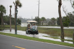 0938---9-28-15 Golf Cart driving through tide water on Sea Island Bike Trail
